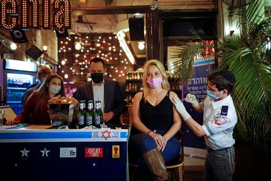 이스라엘의 한 여성이 코로나19 백신을 접종받고 있다. 이스라엘 정부는 무료로 음료와 피자 등을 나눠주며 백신 캠페인을 펼치고 있다. [로이터]