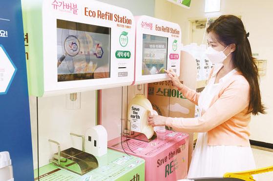 이마트 성수점에서 고객이 에코 리필 스테이션을 통해 섬유유연제를 채우고 있다. 본품 대비 가격을 35~39% 아낄 수 있다. [사진 이마트]