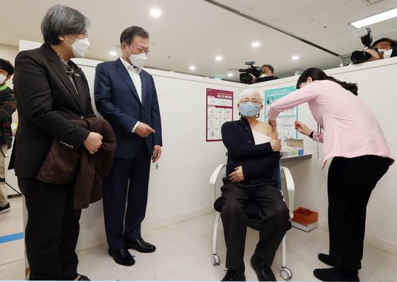 문재인 대통령과 정은경 질병관리청장이 26일 코로나19 백신 접종 참관을 위해 서울 마포구보건소를 방문해 백신 접종을 받는 김윤태 푸르메 넥슨어린이 재활병원 의사를 지켜보고 있다. 뉴시스