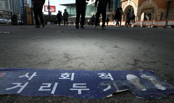 18일 서울 한 임시선별진료소 바닥에 붙은 거리두기 안내문이 낡은 모습이다.   연합뉴스