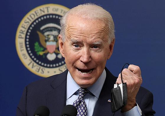 25일(현지시간) 조 바이든 미 대통령이 코로나19 백신 접종자 5000만명 돌파를 기념하는 행사에서 마스크를 들어보이고 있다. 로이터=연합뉴스