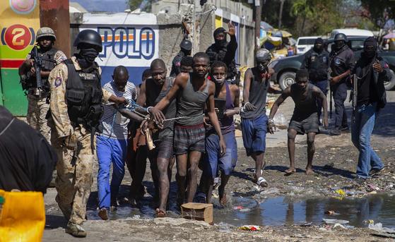 25일(현지시간) 아이티에서 탈옥했다가 붙잡힌 재소자들이 경찰의 지휘를 받으며 이동하고 있다. AP=연합뉴스