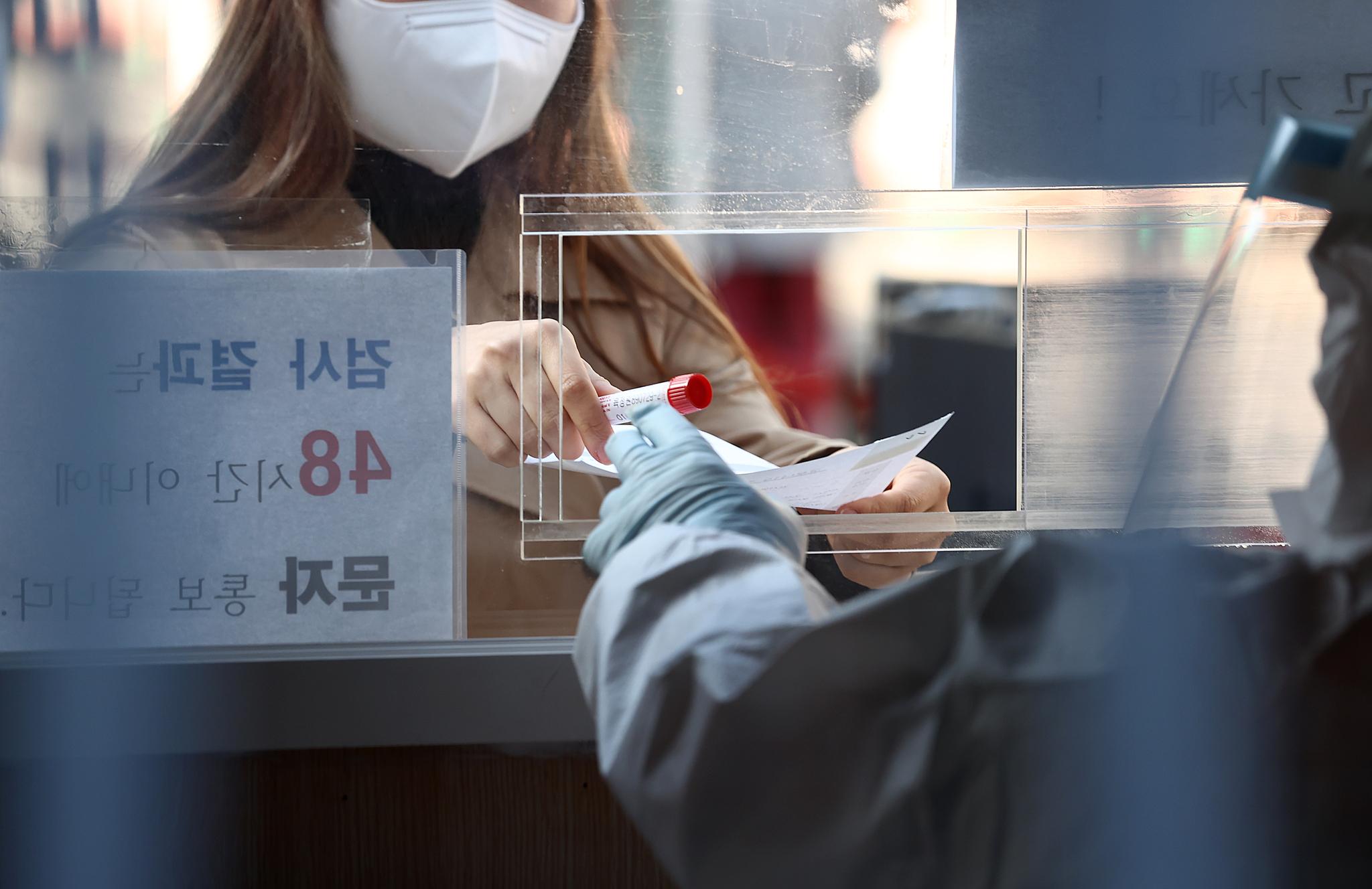 27일 오전 서울역에 설치된 임시선별진료소에서 한 시민이 코로나19 검사를 받은 후 검체를 제출하고 있다. 연합뉴스