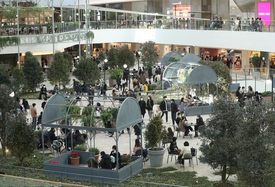 26일 오후 서울 여의도 '더현대 서울'에서 시민들이 쇼핑을 즐기고 있다. 전체 영업면적이 8만9100㎡(약 2만7000평)로 서울 최대 규모다. 이 가운데 절반이 실내 조경과 고객 휴식 공간 등으로 구성됐다. 사진은 시그니처 공간인 5층 사운즈 포레스트. [뉴스1]