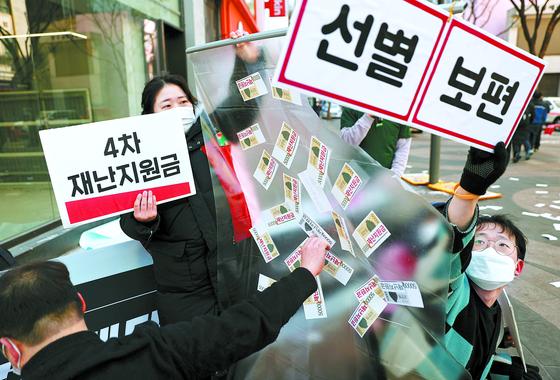 17일 오후 서울 중구 명동거리에서 아르바이트 노동조합이 연 기자회견에서 참가자들이 4차 재난지원금 선별 지급에 반대하는 퍼포먼스를 하고 있다. 연합뉴스