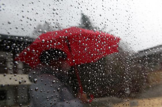 지난 15일 오전 광주 서구 무각사에 주차된 차창에 우산 쓴 시민이 투영되고 있다. 연합뉴스