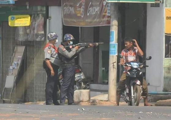 미얀마 군경이 시위와 관련 없는 민간인을 향해 총을 겨누며 위협하고 있다. [SNS 갈무리]