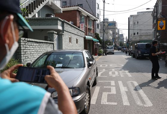지난해 7월 서울시 공무원들이 강남구 일대 어린이보호구역 내 불법 주차를 단속하고 있는 모습. 연합뉴스
