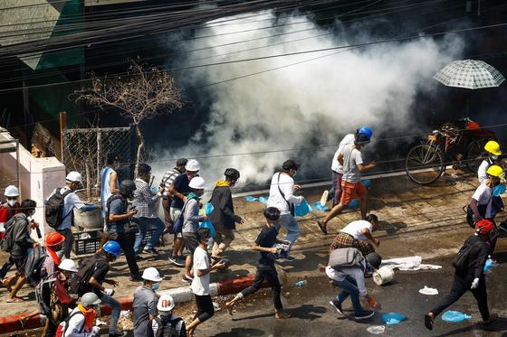 1일(현지시간) 미얀마 양곤에서 군사 쿠데타를 규탄하는 시위대가 최루가스를 피해 달리고 있다. AFP=연합뉴스