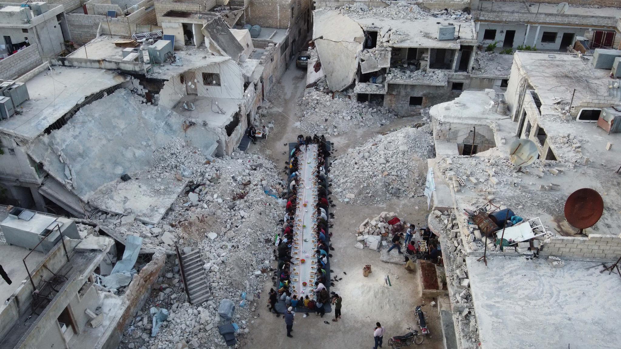 2020년 7월 시리아 알레포 주 아타레브 주민들이 폭격으로 파괴된 마을에서 자선단체의 도움으로 아침 식사를 하고 있다. AFP=연합뉴스