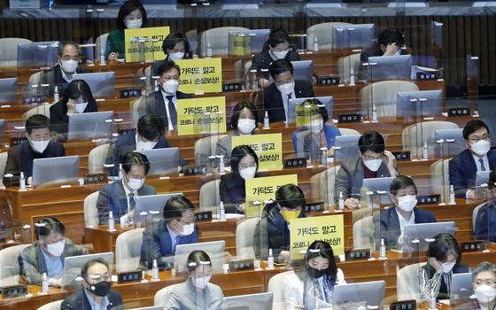 정의당 의원들이 지난달 26일 서울 여의도 국회에서 열린 본회의에서 가덕도 관련 법안을 비판하는 피켓을 의석에 붙여 놓고 있다. 뉴스1