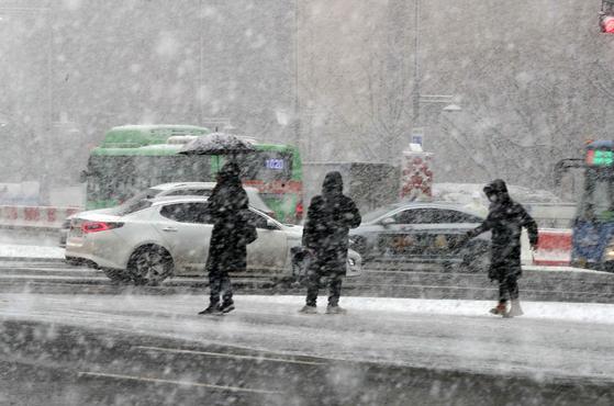 지난 1월 28일 폭설이 내리는 가운데 서울 광화문 앞에서 시민들이 횡단보도를 거너고 있다. 김상선 기자