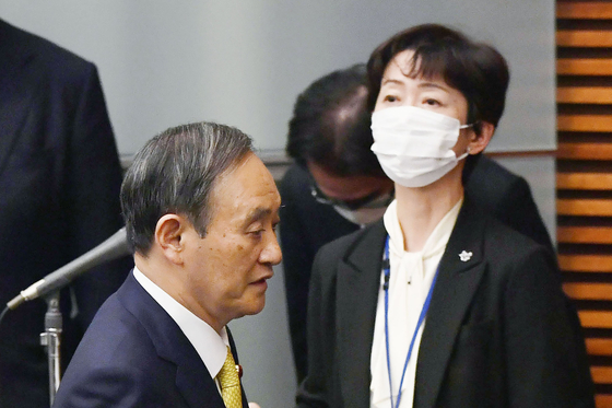 지난해 12월 4일 스가 요시히데 일본 총리가 기자회견장에 들어서며 사회를 맡은 야마다 마키고(오른쪽) 내각 공보관의 앞을 지나고 있다. [AP=연합뉴스]
