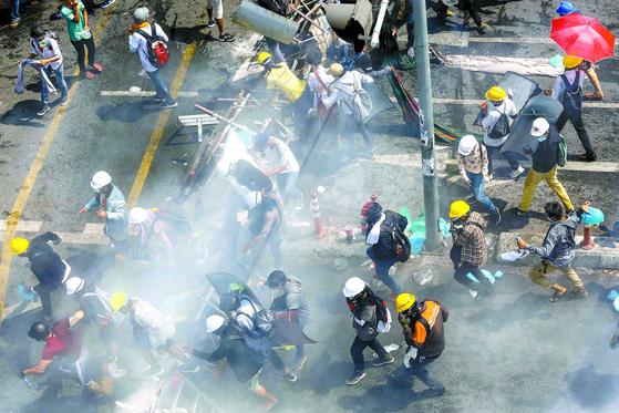 1일 미얀마 최대 도시 양곤에서 쿠데타에 항의하는 시위를 벌이던 시민들이 진압 군경이 발포하자 일제히 달리고 있다. 지난달 28일 군경 발포로 쿠데타 이후 최악의 유혈사태가 발생했지만 시민들은 다시 거리로 나왔다. 28일 하루에만 12~29명이 숨진 것으로 추정된다. [AFP=연합뉴스]