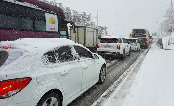 강원 산간과 동해안에 폭설이 쏟아진 1일 오후 동해고속도로 양양나들목 인근에 차량이 거북이 운행을 하고 있다. [사진 양양군]