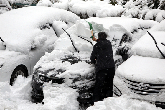 2일 오전 대설경보가 내려진 강원도 강릉에 눈이 펑펑 쏟아지는 가운데 운전자가 출근하기 위해 차에 가득 쌓인 눈을 치워내고 있다. 뉴시스