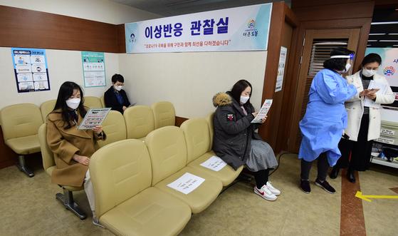 신종 코로나바이러스 감염증(코로나19) 백신 접종이 시작된 지난달 26일 서울 도봉구 보건소에서 요양병원·요양시설 종사자가 아스트라제네카(AZ) 백신 접종을 받은 뒤 이상반응 관찰실에 대기하고 있다. [뉴스1]