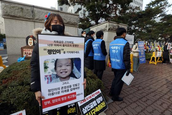 양부모 학대로 숨진 '정인이 사건' 3차 공판이 열린 3일 오전 서울 양천구 남부지방법원 앞에서 시민이 양부모의 법정 최고형을 촉구하는 손팻말을 들고 있다. 뉴스1