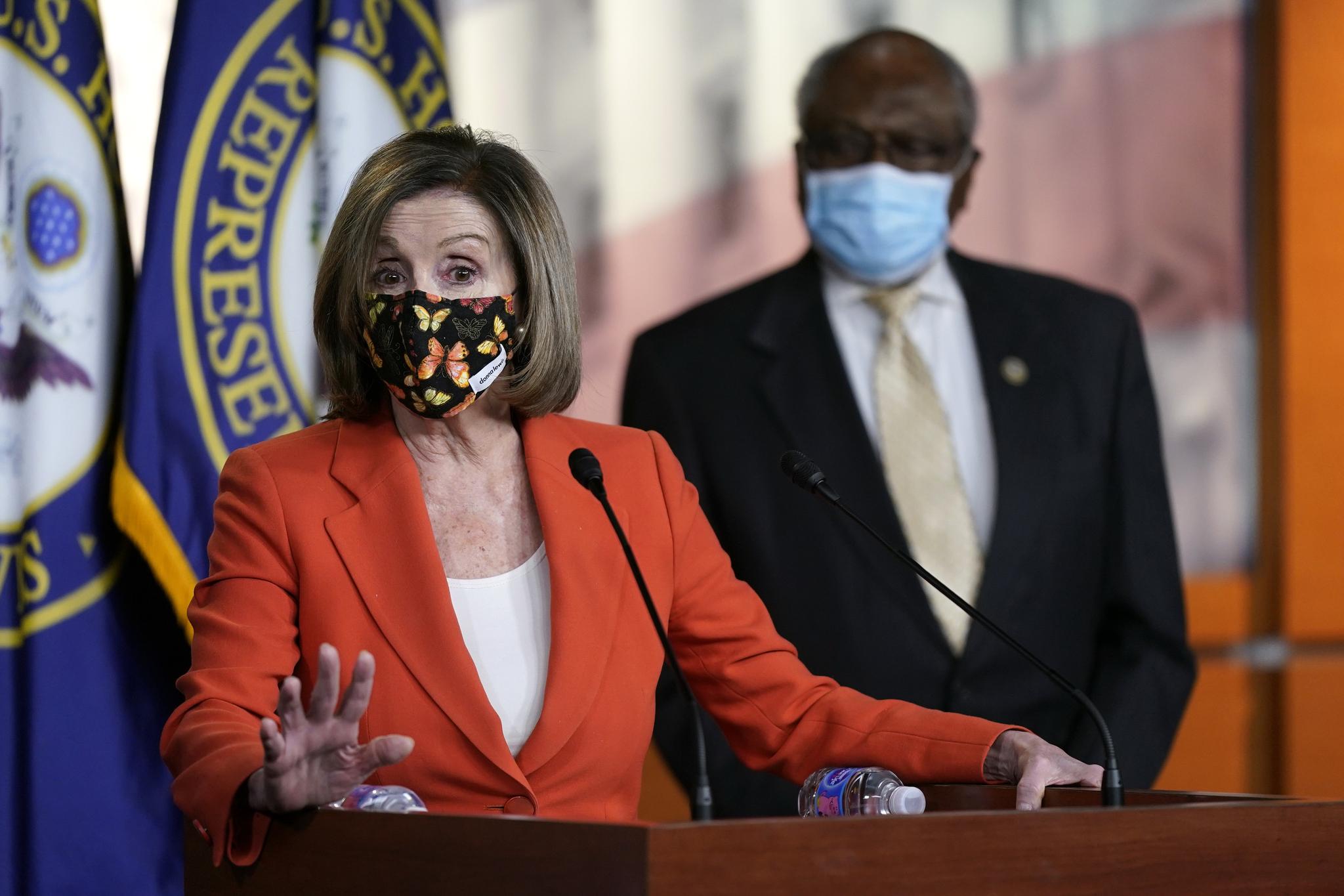 2일 기자회견하는 낸시 펠로시 하원의장. 마스크의 나비 색상과 재킷 색상이 조화를 이룬다. 뒤에 선 남성의 평범한 마스크와 뚜렷하게 비교된다. AP=연합뉴스