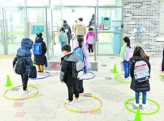 2일 전북 전주 효천초등학교에서 학생들이 훌라후프로 표시해 놓은 거리두기를 지키며 교실에 들어서고 있다. [뉴시스]