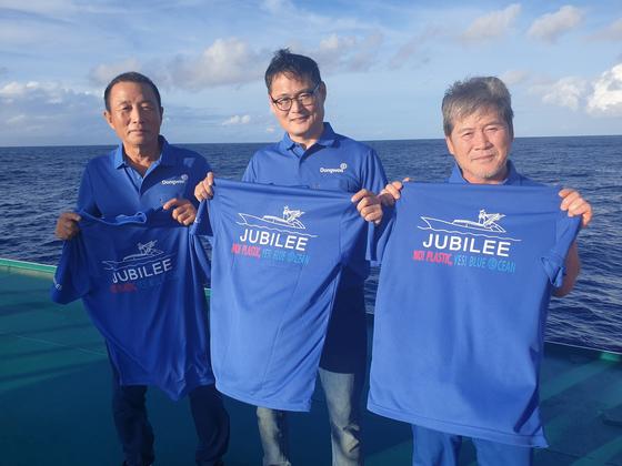 동원산업 임직원들이 해양 투기 플라스틱을 줄이자는 의미의 글귀가 세겨진 티셔츠를 들고 있다. 사진 동원산업
