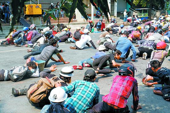 지난 3일(현지시간) 미얀마 제2 도시인 만달레이에서 경찰이 발포하자 시위대가 황급히 땅바닥에 엎드리고 있다. [로이터=연합뉴스]