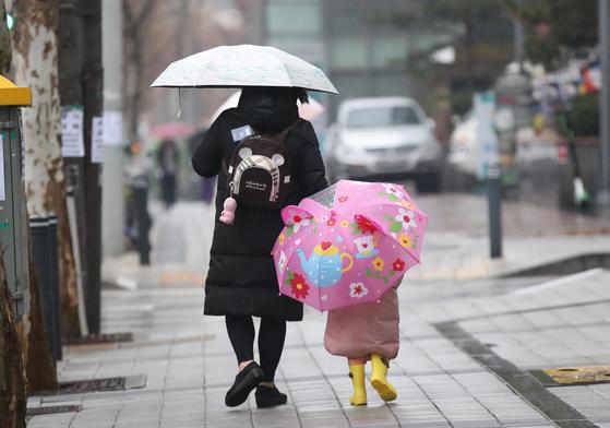 비가 내린 지난 1월 21일 오후 서울 마포구 상암동에서 한 어린아이가 토끼 귀모양한 우산에 노란 부츠까지 갖춰신고 어머니 뒤를 따라걷고 있다. 우상조 기자