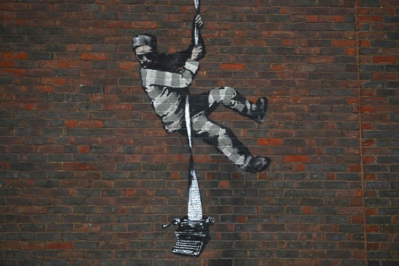 2일(현지시간) 영국 레딩시에 있는 옛 레딩 교도소 담장 벽면에 뱅크시의 새 작품으로 추정되는 벽화가 그려져 있다. AFP=연합뉴스