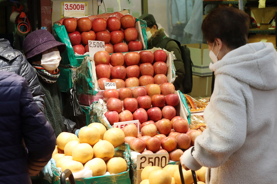 설 연휴를 앞둔 지난달 10일 서울 동대문구 청량리 청과물시장에서 시민이 과일을 살펴보고 있다.뉴스1