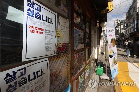 지난 2일 오전 서울 성북구 한 가게에 불어 있는 영업제한 조치로 생존권 위협과 억울함을 호소하는 포스터. 연합뉴스