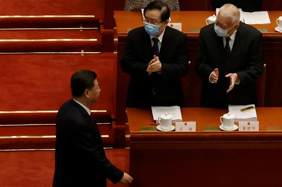 둥젠화(오른쪽) 전 홍콩 행정장관이 5일 오전 베이징 인민대회당에서 열린 전인대 개막식에서 시진핑(왼쪽) 중국 국가주석이 입장하자 일어서 박수를 치고 있다. [연합뉴스=로이터]