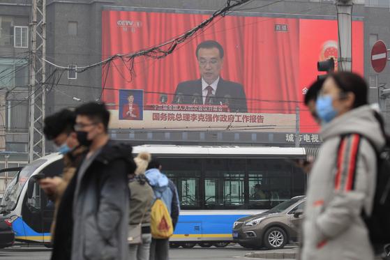 5일 중국 전국인민대표대회 연례 전체회의가 개막됐다. 리커창 총리의 연설 장면이 나오는 대형 전광판을 배경으로 베이징 시민이 거리를 지나가고 있다. EPA=연합뉴스