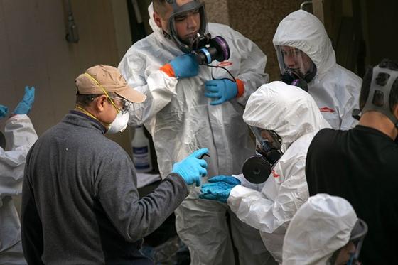 미 워싱턴주 커클랜드의 장기 요양시설 라이프케어센터에서 방역요원들이 건물 밖으로 나와 방호복을 벗고 손을 소독하고 있다. AFP=연합뉴스