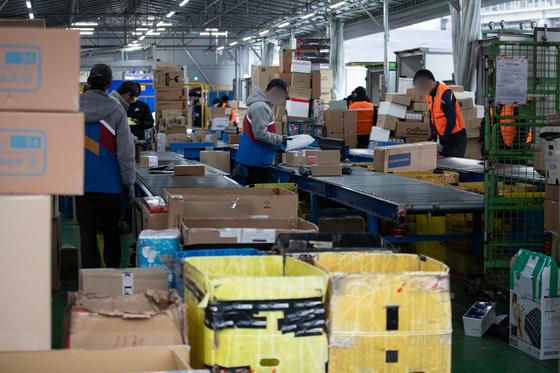 서울 시내의 한 택배 물류센터에서 택배 노동자들이 배송 준비작업을 하고 있다.  [뉴스1]