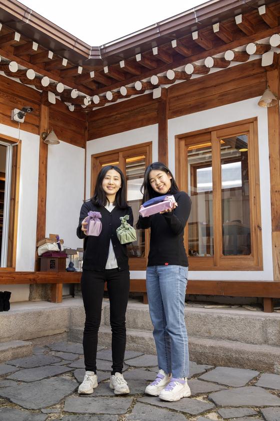 안효빈(왼쪽)·김태인 학생모델이 직접 만든 보자기 아트 작품을 들고 포즈를 취했다. 준비물·물병 포장 등 실생활 사용 목적으로도, 소중한 이를 위한 선물 포장으로도 활용할 수 있다.