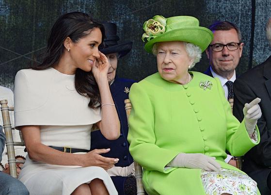 마클 왕자비가 왕실에 들어온 초기였던 2018년 6월의 모습. 여왕 엘리자베스 2세의 이야기를 경청하고 있다. AFP=연합뉴스