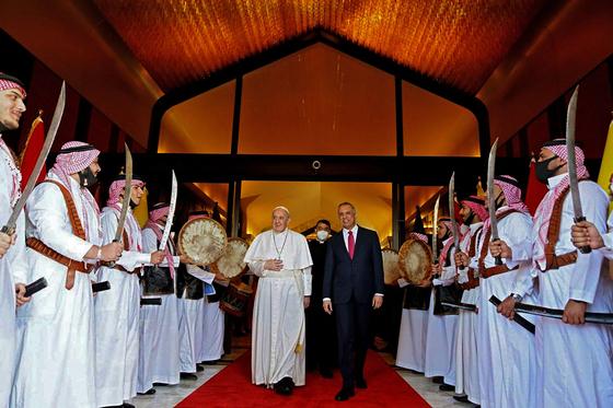 지난 5일 이라크 바그다드 공항에 도착한 프란치스코 교황이 무스타파 알카드헤미 총리의 영접을 받으며 의장대를 사열하고 있다. [AFP=연합뉴스]