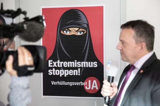 7일(현지시간) 발토 보프만 스위스 국민당 의원이 '극단주의 그만'이라고 쓴 캠페인 포스터를 배경으로 방송 인터뷰를 하고 있다. [EPA=연합뉴스]