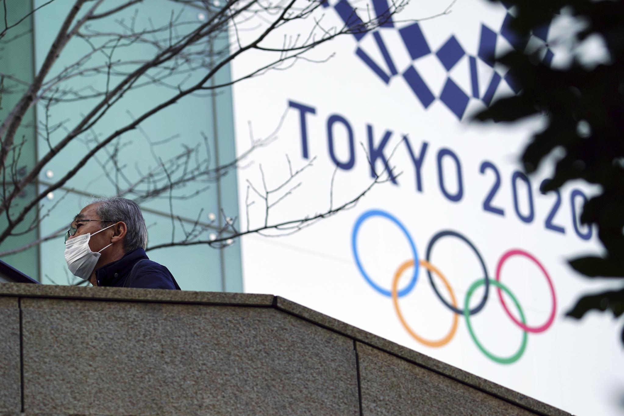 마스크를 쓴 한 남성이 지난 2월 25일 도쿄 올림픽 현수막 앞을 걷고 있다. AP=연합뉴스