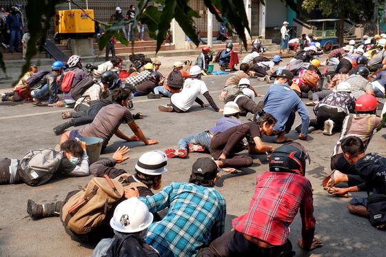 지난 3일(현지시간) 미얀마 제2 도시인 만달레이에서 경찰이 발포하자 시위대가 황급히 땅바닥에 엎드리고 있다. 로이터=연합뉴스