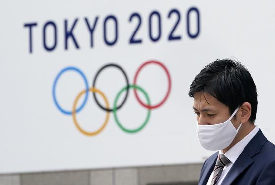한 남성이 일본 도쿄도 청사 앞에 걸린 도쿄올림픽 광고판을 지나고 있다. EPA=연합뉴스