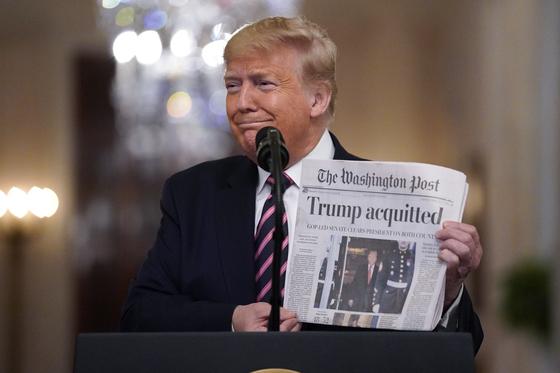 트럼프 대통령이 지난달 6일(현지시간) 백악관에서 자신의 탄핵안 부결이 적힌 워싱턴포스트를 들어보이고 있다. [AP=연합뉴스]