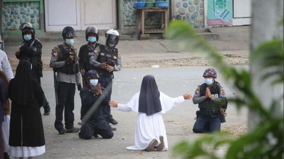 안 로사 누 따웅 수녀가 8일(현지시간) 미얀마 북부 카친주 미치나시에서 시위대를 진압하러 온 경찰들 앞에 무릎을 꿇고 '발포를 자제해 달라'고 호소하고 있다. 경찰 두 명도 함께 무릎을 꿇고 손을 모았다. [SNS 캡처]