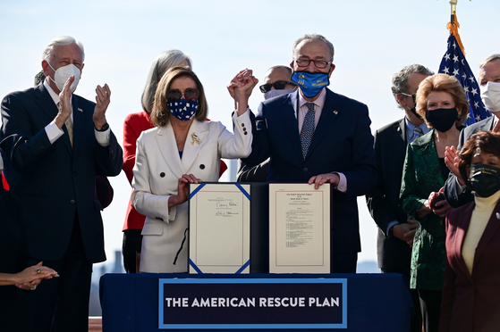 낸시 펠로시 미국 하원의장(왼쪽에서 두번째)과 척 슈머(펠로시 의장 오른쪽) 미 민주당 상원 원내대표가 10일(현지시간) 워싱턴 연방 의사당에서 경기부양법안에 서명한 뒤 손을 들고 환호하고 있다.[로이터=연합뉴스]