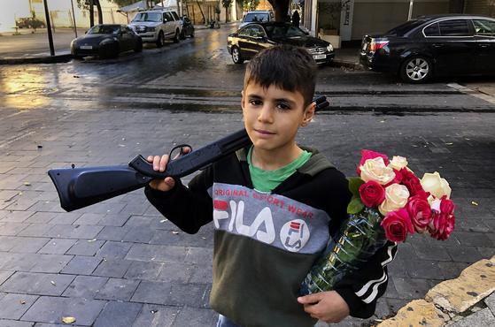 시리아에서 내전을 피해 가족과 함께 이웃 레바논의 수도 베이루트로 피난 온 10세 소년 오마르가 지난 1월 31일 거리에서 장난감 총과 꽃을 들고 있다. 유니세프는 10년에 걸친 시리아 내전으로 시리아 어린이 1만2000명이 숨지거나 부상을 입었다고 밝혔다. 수백 만의 어린이가 학교에 가지 못하고 있으며 상당수는 영양실조를 겪고 있다. 10년에 걸친 내전으로 최대 59만이 숨지고 100만 이상이 부상을 입었으며 500만의 난민을 포함해 전체 인구의 절반이 살던 곳을 떠났다. 21세기에 맞은 인도주의 재앙이다. AP=연합뉴스