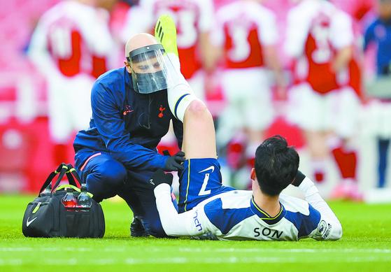 손흥민이 허벅지 통증을 호소하자, 메디컬팀이 투입돼 부상 부위를 살피고 있다. [AP=연합뉴스]