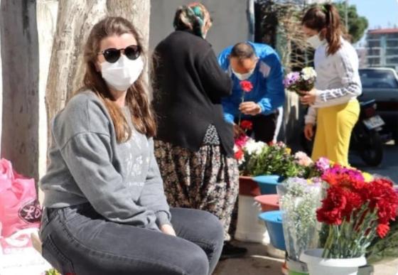 메르베 보즈쿠르트가 꽃을 팔는 어머니 옆에 앉아 있다. 두 사람의 이야기는 '영국 명문 옥스퍼드대에 다니는 딸과 헌신적인 어머니의 감동 스토리'로 터키 현지 방송에 소개됐다. [트위터 캡처]