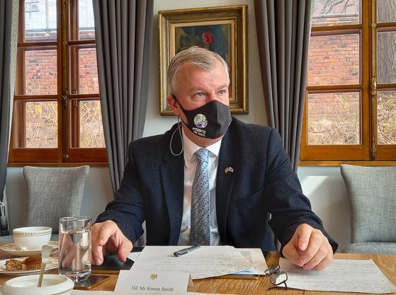 사이먼 스미스 주한영국대사가 18일 관저에서 영국의 외교 정책에 대해 설명하고 있다. 대사가 착용한 마스크엔 영국이 올해 야심차게 개최하는 유엔 기후변화당사국총회(COP26) 마크가 그려져 있다. 제니 홍 주한영국대사관 공보관 제공