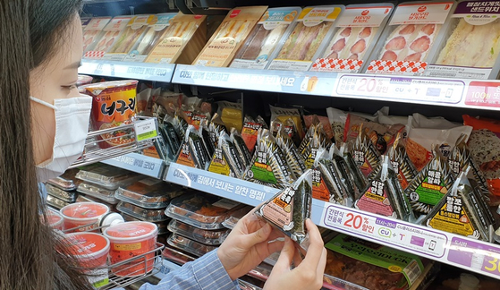 리뉴얼 된 삼각김밥을 살펴보는 소비자. [사진 CU]