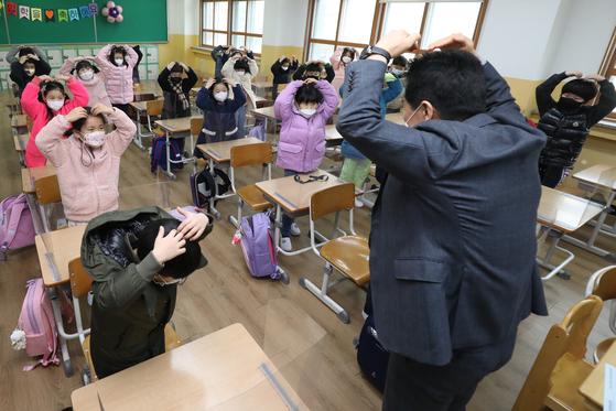 지난 2일 오전 대구의 한 초등학교 1학년 신입생들이 투명 가림막이 설치된 교실에서 교장선생님과 인사를 나누고 있다. 뉴스1